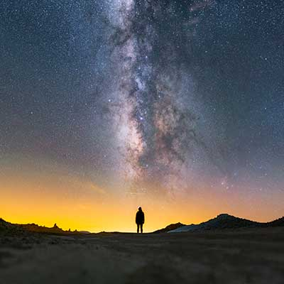 Photo of person standing under Milky Way galaxy