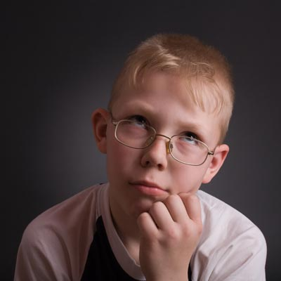 Photo of boy with hand on chin and questioning look