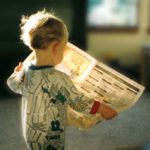 Photo of child reading a newspaper