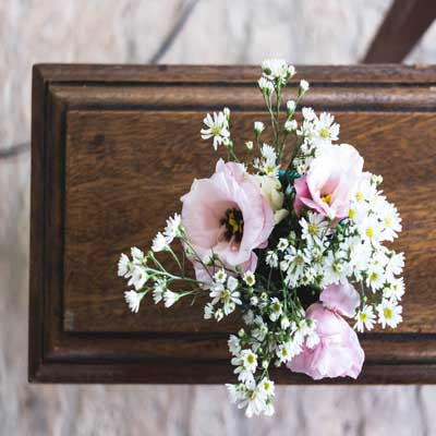 Photo of funeral casket with pink and white flowers