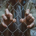 Photo of a man gripping a mesh fence