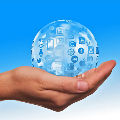 Hand holding up globe with social media icons