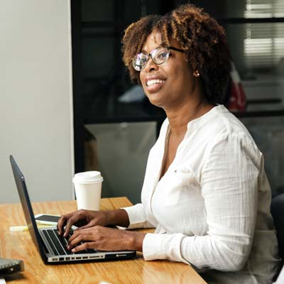 Photo of woman at desk typing on laptop computer